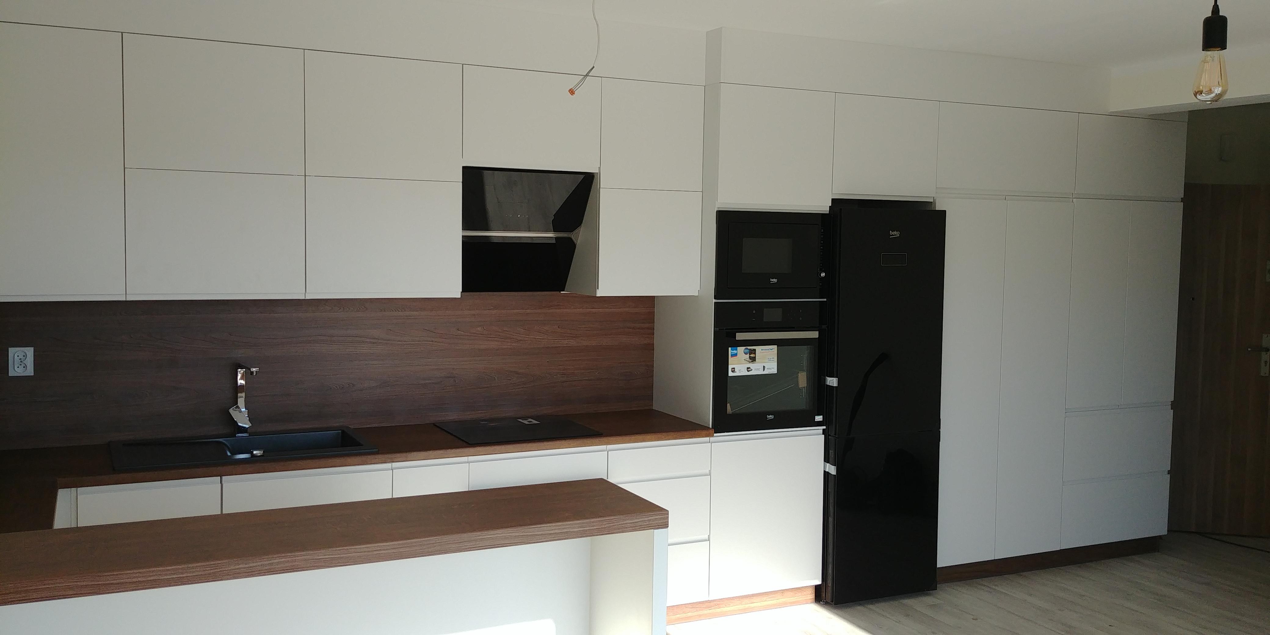 Blat oraz płyta w tym samym kolorze zamontowana między meblami optycznie powiększają kuchnie
