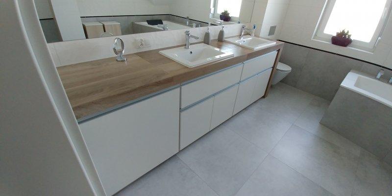 Zabudowa łazienki, jasne fronty z blatem w kolorze drewna